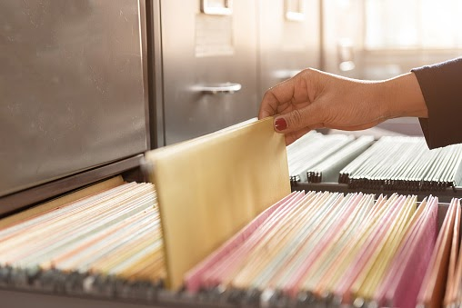a woman sifting through a filing cabinet