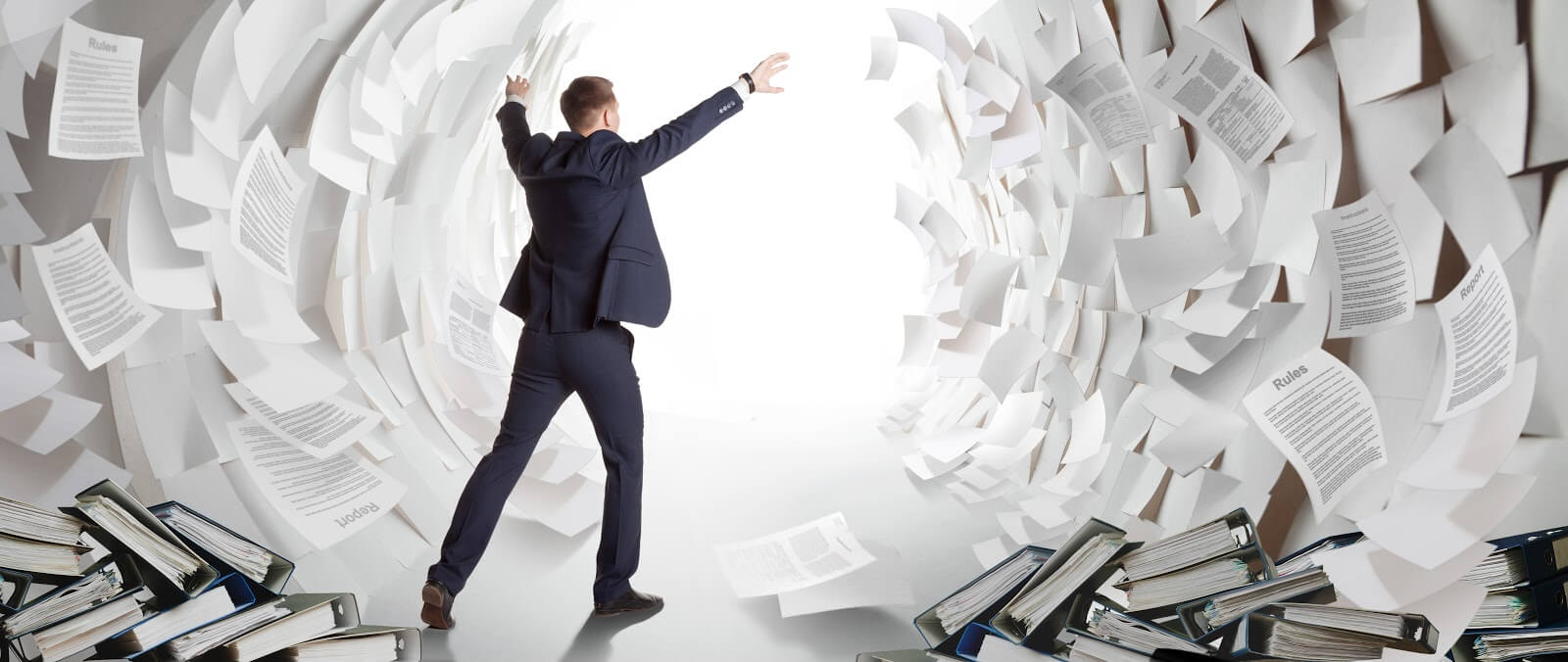 a man looking overwhelmed by a stack of paper